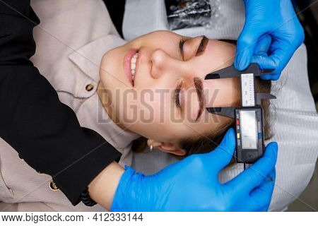 Woman With Permanent Makeup Tattoo On Her Eyebrows. Close-up Beautician Makes A Sketch Of The Eyebro