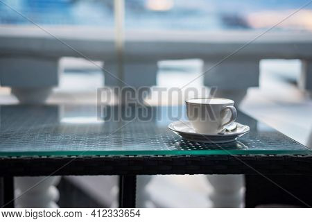 White Cup Of Cappuccino, Hot Coffee On Brown Glass Table In The Cafe