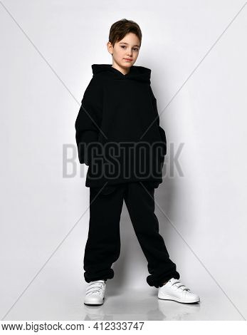 Studio Shot Of A Small Schoolboy In A Black Warm Fleece Sportswear Posing For The Camera Isolated On