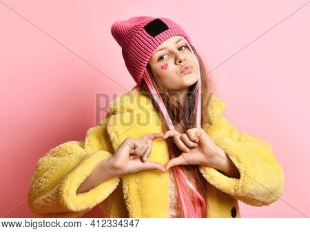 Bright Teen Girl Showing Heart To Camera While Standing On Pink Background. Girl In A Hat, Yellow Fu
