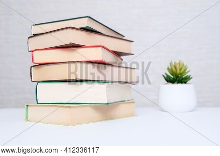 A Stack Of Books Lying On A White Table, Reading And Education Concept