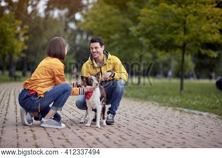 young caucasian people getting know each other by talking about pets in autumn park
