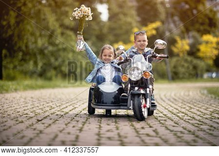 cute caucasian boy driving little girl in sidecar of motorcycle toy on battery in park