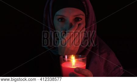 A Woman In Grief Holding A Burning Red Candle And Covering Her Mouth With Palm