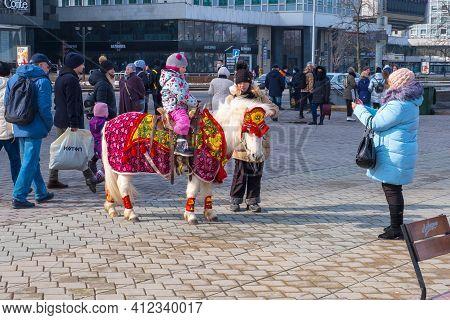 Minsk, Belarus - March 13, 2021: Little Girl Riding A Pony. Street Celebrations Of Maslenitsa In The