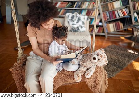 A young mother and her little daughter sitting on the swing in a relaxed atmosphere at home and enjoying while reading a book together. Family, together, leisure