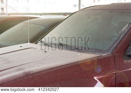 Windshield Wipers Of A Dirty Red Car Covered With A Layer Of Dust And Dry Dirt, A Closeup Of A Part