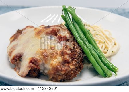 Breaded Chicken Parmesan Served With Cheesy Pasta And Topped With Green Beans For A Delicious Dinner