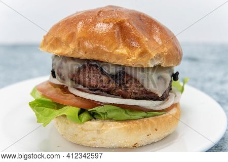Stacked Hamburger With Melted Cheese Sitting On Onion, Tomatoes, Lettuce, And Bun For A Delicious Me