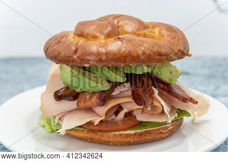 Unique Chicken Club Sandwich Served On A Pretzel Bun And Loaded With Avocado Wedges, Bacon, Meat, An