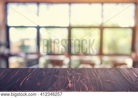 Wooden Dark Board Empty Table Top On Of Blurred Background. Perspective Brown Wood Table Over Blur I