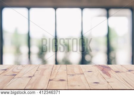 Wooden Board Empty Table Top On Of Blurred Background. Perspective Brown Wood Table Over Blur In Cof