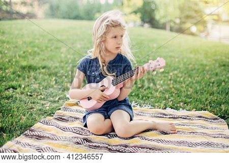 Cute Adorable Blonde Girl Playing Pink Guitar Toy Outdoor. Child Playing Music And Singing Song In P