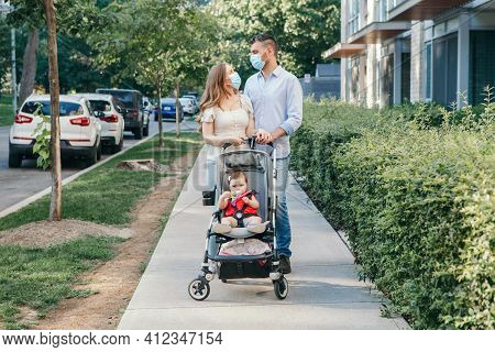 Caucasian Mother And Father In Face Masks Walking With Baby In Stroller. Family Strolling Together O