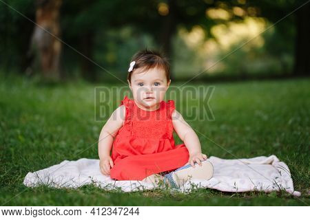 Funny Baby Kid. Cute Adorable Baby Girl In Red Dress Sitting On White Blanket In Park Outdoor. Funny
