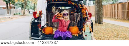 Trick Or Trunk. Child Girl Celebrating Halloween In Trunk Of Car. Kid With Red Carved Pumpkin Celebr
