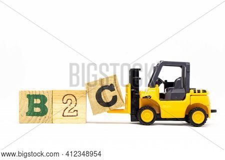 Toy Forklift Hold Letter Block C To Complete Word B2c (abbreviation Of Business To Consumer) On Wood