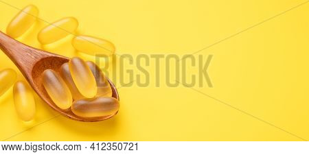 Close Up Omega 3 Capsules In Wooden Spoon On Yellow Background. Fish Oil Softgels. Horizontal Banner