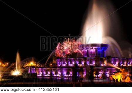 Buckingham Fountain Grant Park Chicago At Night Illuminated In Purple At Night, With Fireworks In Th