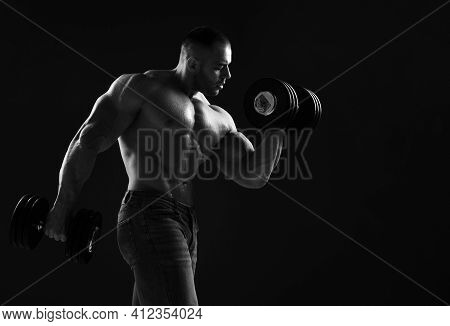 Muscular Men Weightlifter Is Working Out In Gym, Lifting Alternately Two Big Heavy Dumbbells, Doing