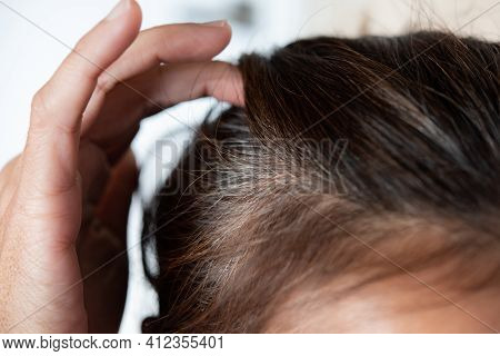 Going Gray. Young Woman Shows Her Gray Hair Roots.
