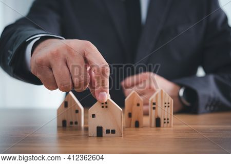 Businessman Hand Choosing Mini Wood House Model From Model On Wood Table,  Planning To Buy Property.