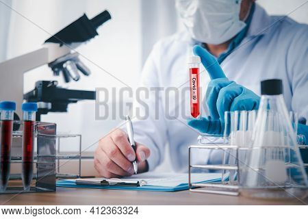 Microbiologist With A Tube Of Biological Sample Contaminated By Coronavirus With Label Coronavirus,