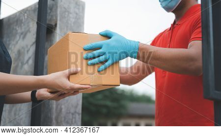 New Normal Life Style. Home Delivery Shopping Box Man Wearing Gloves And Protective Mask Delivering