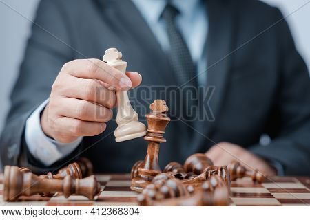 Businessman Moving Chess Piece On Chess Board Game Concept For Ideas And Competition And Strategy, B