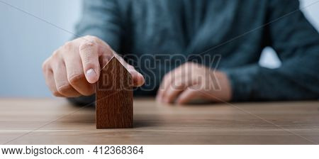 Man Hand Choosing Mini Wood House Model From Model On Wood Table, Planning To Buy Property. Concept