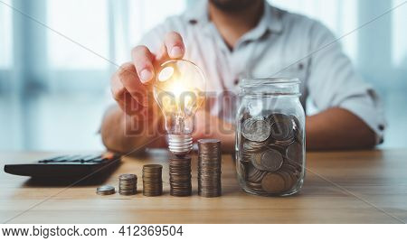 Saving Energy And Money Concept. Idea For Save Or Investment. Businessman Touch Lightbulb On Coins S