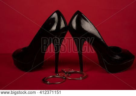 Bdsm Role Play Concept. Sexual Behaviour. Shoe On High Heel With Handcuffs On Red Background