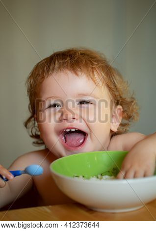 Smiling Baby Eating Food. Cutr Baby Child Eating Himself With A Spoon. Launching Child Eating Food