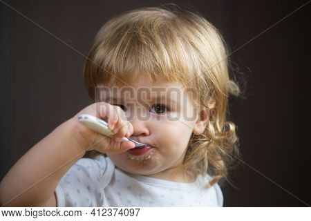 Baby Eating With Dirty Face. Cheerful Smiling Child Child Eats Itself With A Spoon Baby Eating With