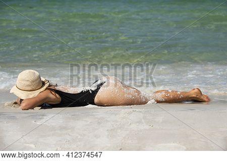 Summer Beach Vacation. Woman In Black Swimwear Lying On Sandbeach. Girl Enjoying Sunbath Near Sea. S