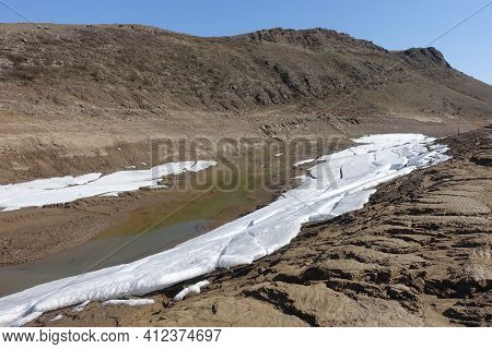Harsh Natural Landscape And Road Along The Riverbed And Mountains For Off-road Suv With Puddles Of S