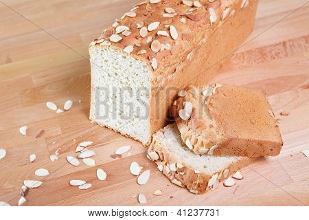 Loaf of gluten-free almond bread indoors on a wooden table