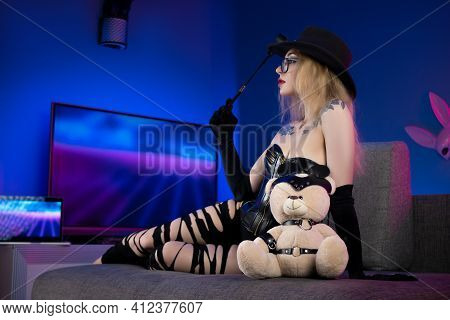 Sexy Woman In A Corset And Torn Pants On The Couch With A Whip And A Teddy Bear In Bdsm Accessories