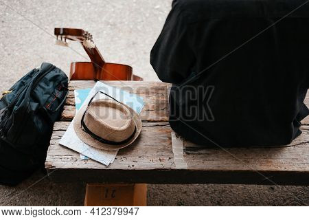 Backpack And Hat With Map  At The Train Station With A Traveler Sitting On Bench While Waiting Train