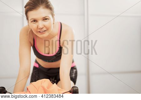 Woman Trains At Home On A Stationary Bike During A Pandemic.