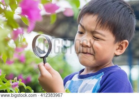 Portrait Of Happy Asian Child Boy Holding And Looking With Magnifying Glass On The Flower Tree And G