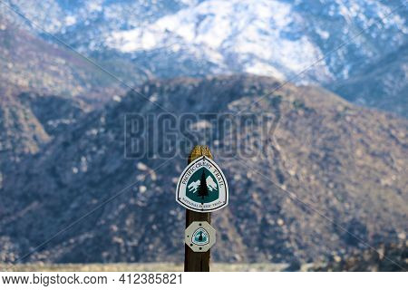 March 13, 2021 In Snow Creek, Ca:  Pacific Crest Trail Sign Post With Barren Mountains Covered With