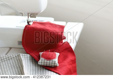 Pillow With Needles For Sewing On A Background Of Red Fabric And A Sewing Machine On The Table. Sewi