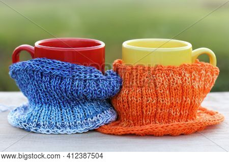 Colored Knitted Scarves On Mugs. A Warming Drink For Two