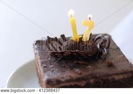Piece Of Chocolate Cake With Burning Candles In The Form Of Numbers. Sweet Seventeenth Birthday