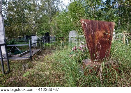 Old Cemetery. Graves And Monuments Are Bent And Overgrown With Grass And Trees. Russia, Krasnoyarsk,