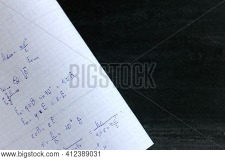 Copybook Abstract With Formulas On Black Chalkboard Background. Solving Problems In Physics