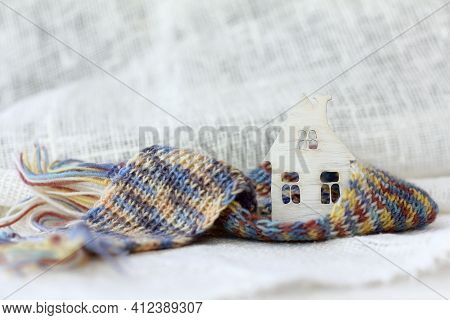 Small Wooden House With A Pipe Wrapped In A Scarf On A Background Of Light Fabric. Warming Technolog
