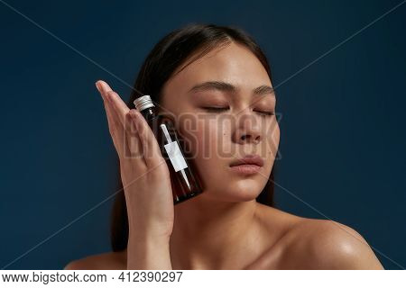 Young Girl Closing Her Eyes And Holding A Bottle Of Skin Care Product. Asian Model With A Naked Top