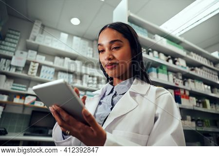 Low Angle View Of Woman Pharmacist Wearing Labcoat Uniform Using Digital Tablet
